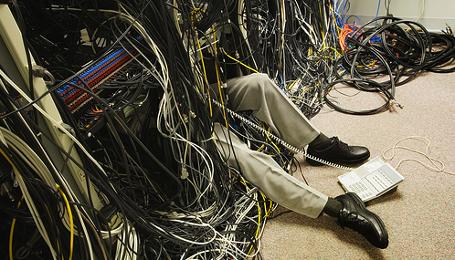 IT Engineer buried under a pile of messy network cabling.